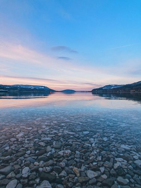 ShotOnIphone Attersee Austria Tranquil Scene Sunset Beauty In Nature Pebble Scenics Nature Tranquility Outdoors No People Mountain Sky Beach Blue Pebble Beach Day Sea Water