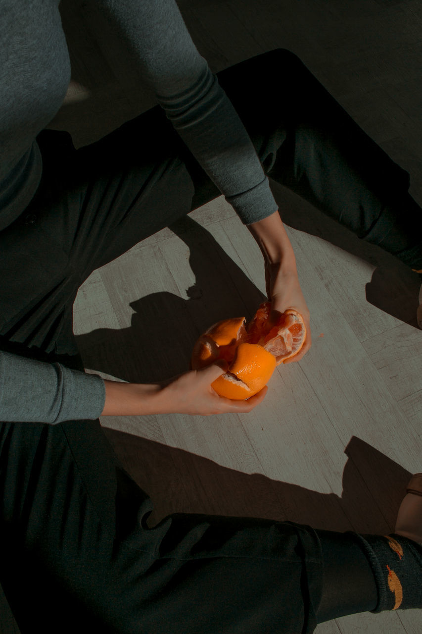 High Angle View Of Cropped Hands Peeling Orange In Darkroom