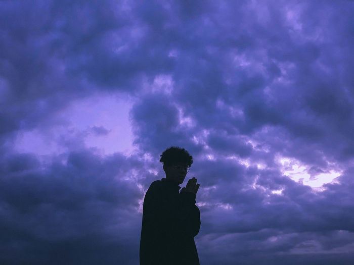 Low angle view of silhouette man standing against sky