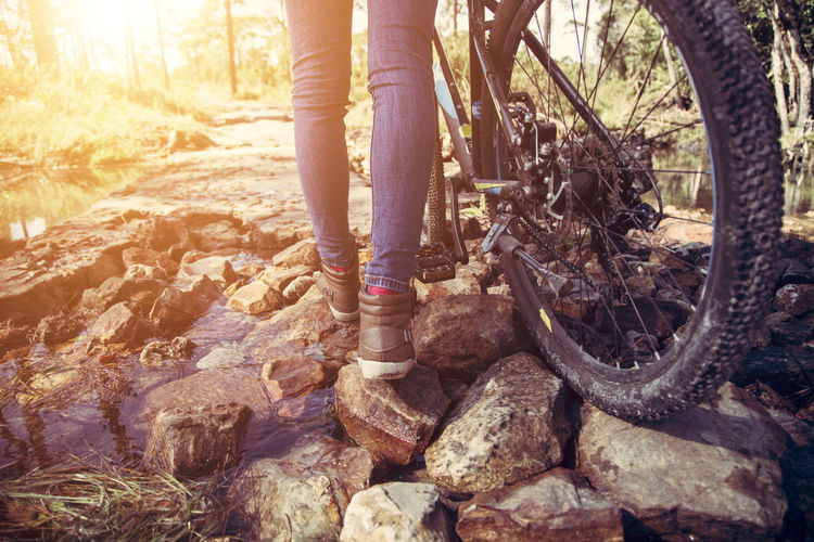Close up legs and bicycle adventure in travel Low Section Body Part Human Body Part One Person Human Leg Rock Solid Leisure Activity Bicycle Standing Day Nature Sunlight Rock - Object Lifestyles Real People Adult Women Outdoors Human Foot Jeans Wheel Human Limb Strong Exercise