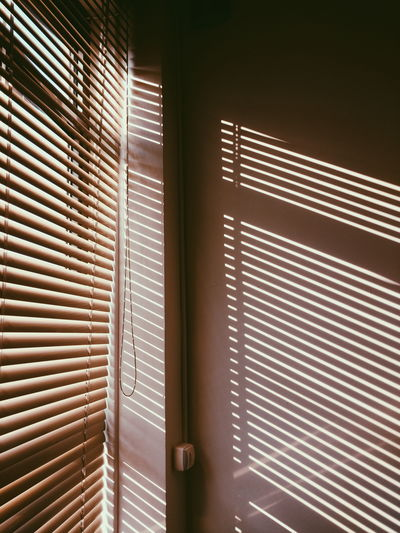 Sunlight Streaming Through Blinds On Wall