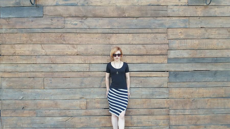 Young woman standing against wooden wall
