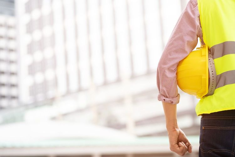 Midsection of engineer holding hardhat standing against building