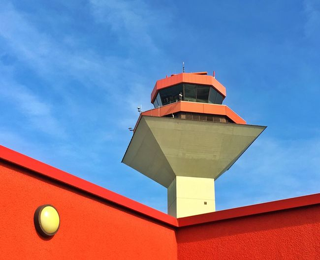 Low angle view of air traffic control tower against blue sky