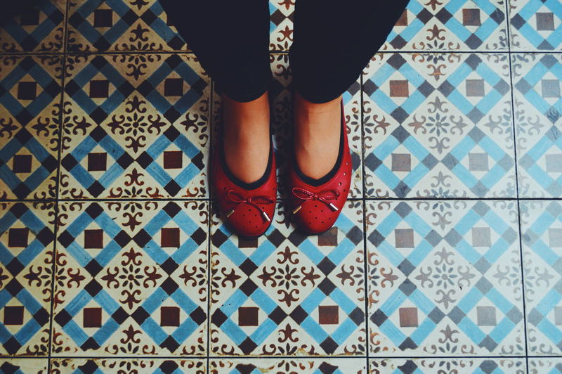 Low section of woman with red shoes standing on tiled floor