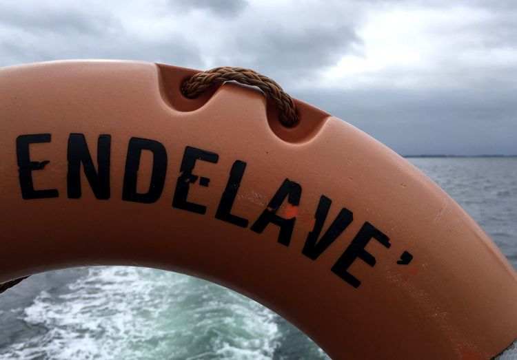 Close-up of text on life belt against sea