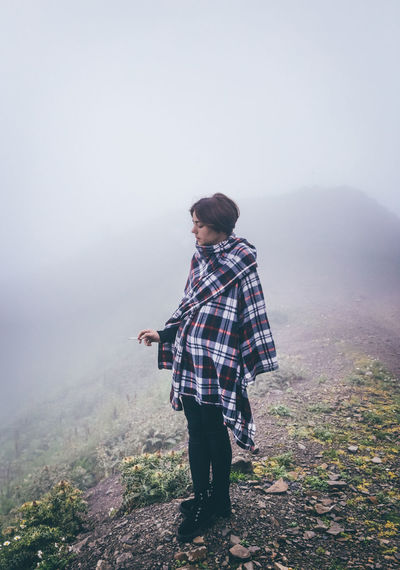 Young woman wrapped in blanket during foggy weather