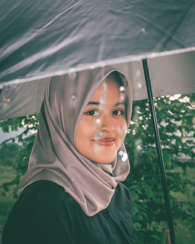 Portrait of smiling teenage girl holding umbrella standing outdoors