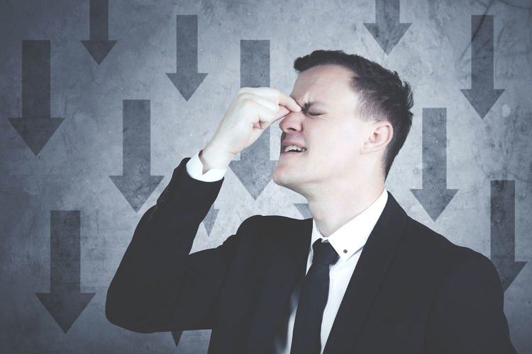 Stressed businessman standing against wall