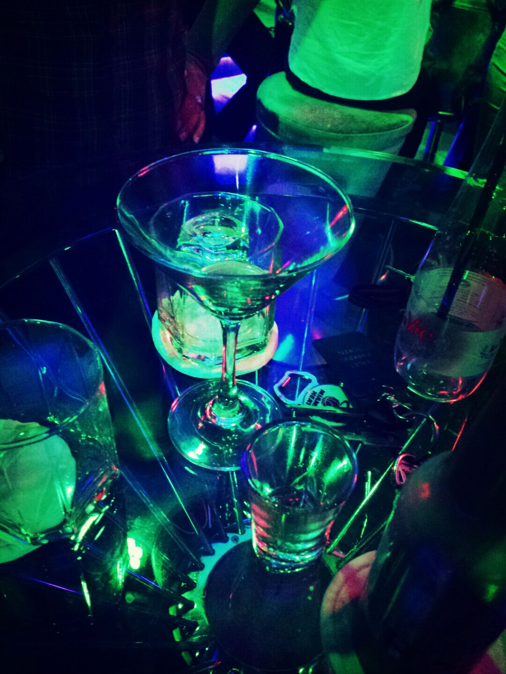 indoors, water, drinking glass, glass - material, transparent, refreshment, drink, close-up, reflection, wineglass, high angle view, glass, green color, food and drink, alcohol, freshness, table, bottle, no people
