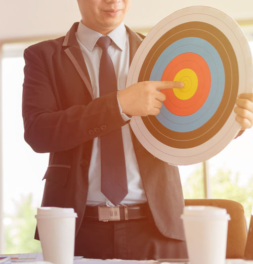 Businessman Holding Dartboard In Office