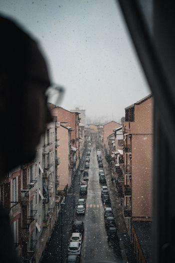 City buildings seen through wet window