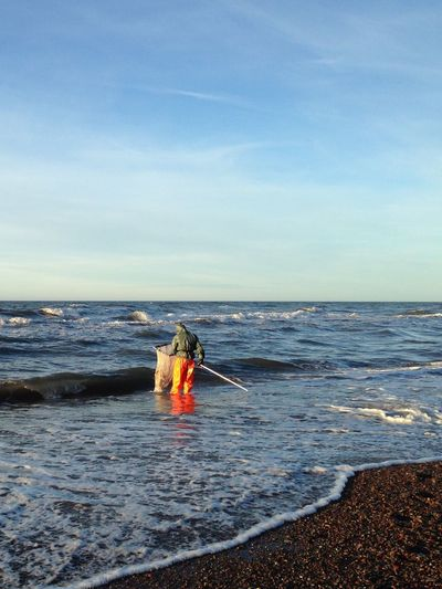 Rear view of man cleaning litter at sea shore
