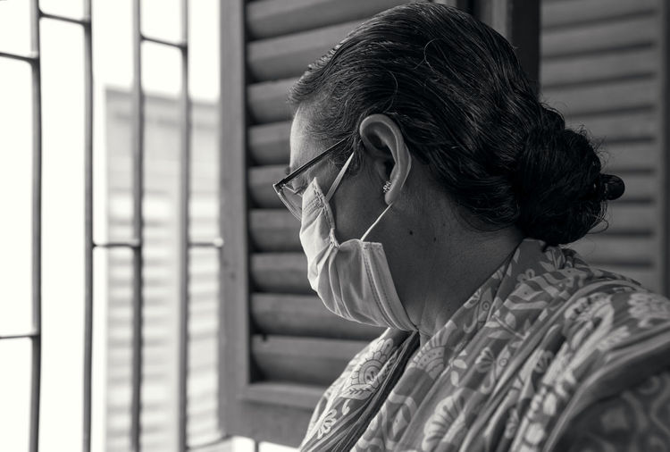An aged bengali woman wearing surgical face mask, casually looking out of window