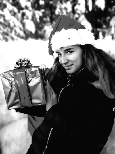 Portrait of smiling young woman holding christmas present while standing outdoors