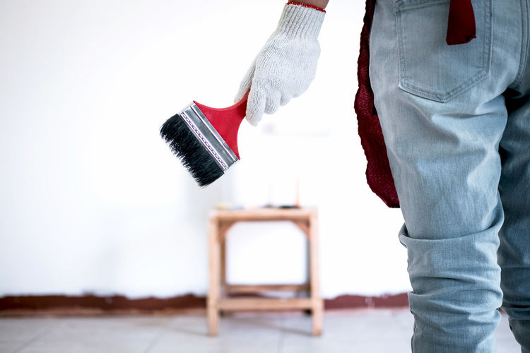 Midsection Of Man With Paintbrush Standing On Floor At Home