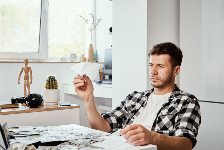Man with laptop and dollar banknotes plays with paper plain