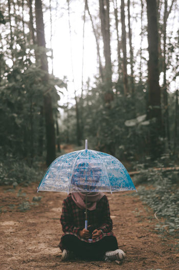 Full Length Of Woman With Umbrella Sitting In Forest
