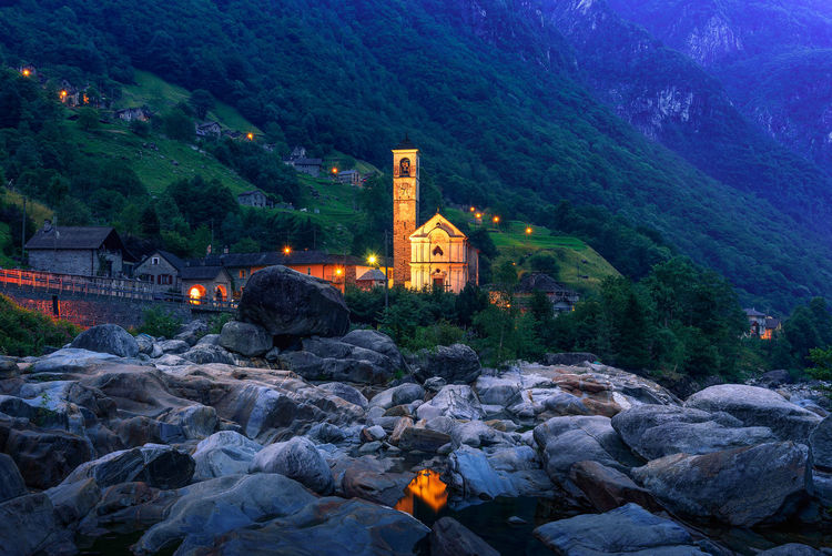 Illuminated buildings by mountain against trees and mountains