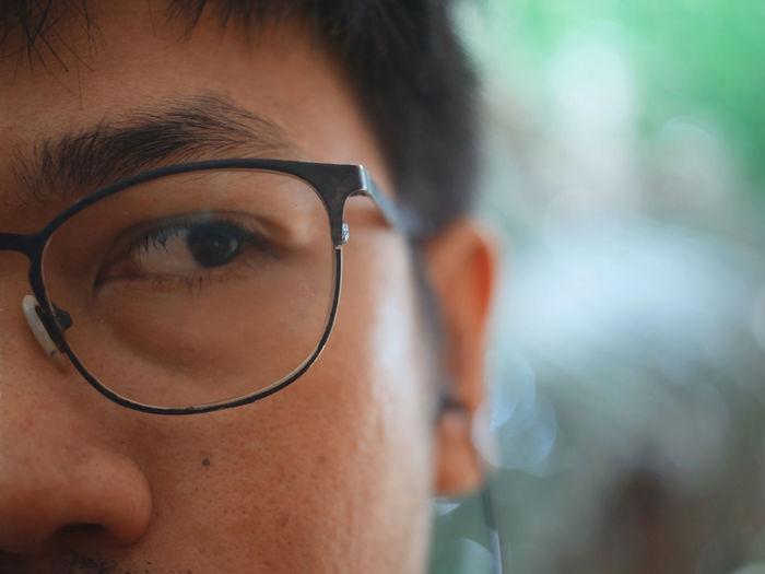Close-up of man wearing eyeglasses looking away