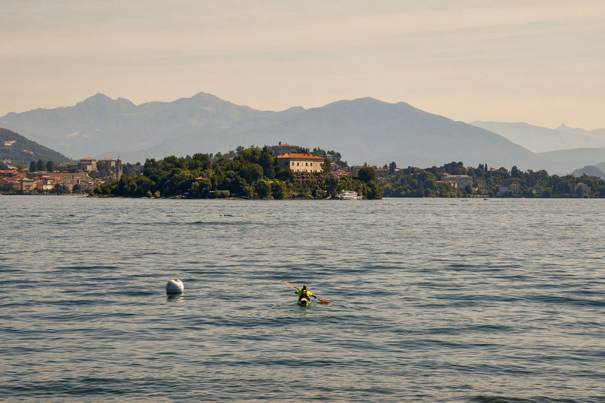 Kayak on the Maggiore Lake with Madre Island and coast at sunset, Piedmont, Italy Mountain Water Waterfront Mountain Range Beauty In Nature Nature Scenics - Nature Outdoors Adventure Sport Real People Transportation People Tourism Tourist Kayak Kayaking Isola Madre Island Lake Maggiore Lake Piedmont Italy Sunset Travel Vacations