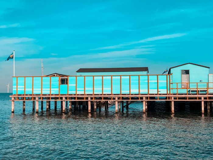 View of stilt house over sea against blue sky