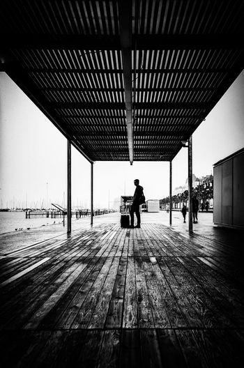 Rear view of man walking on wooden floor