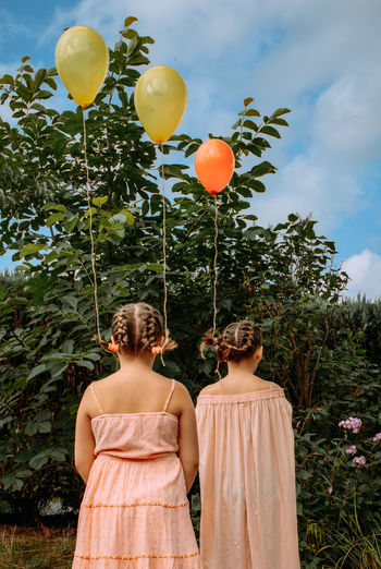 Two sisters in pink dresses are on the street. balloons are tied to their braided hair