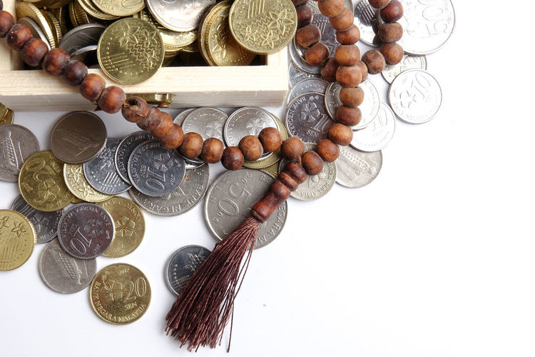 Directly above shot of rosary beads with coins in wooden box on white background