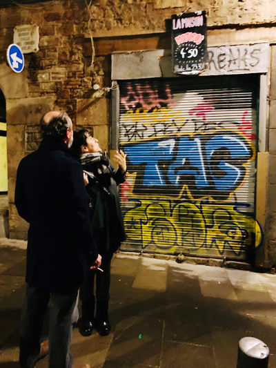 Rear view of people standing against graffiti wall