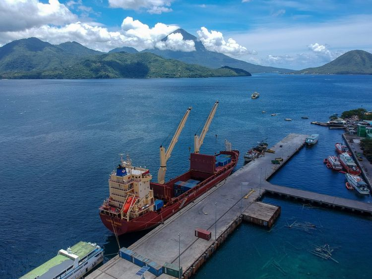 Aerial photograph of cargo vessel unloading in Ternate Harbour, Maluku, Indonesia. Maluku  INDONESIA Cargo Vessel Maritime Color Image Aerial Photography Harbor Merchant Ship Trade Shipping  Ternate Volcano Dock Cargo Ship Nautical Vessel Water Mountain High Angle View Transportation Sea Mode Of Transport Day Outdoors Sky Scenics Cloud - Sky Beauty In Nature Mountain Range No People