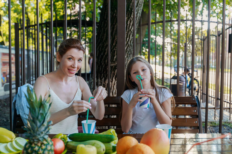 Mother and daughter drinking juice while sitting at restaurant