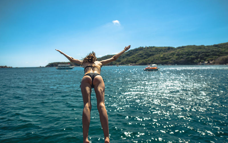 Rear View Of Young Woman Diving In Sea Against Sky