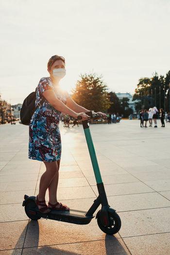Full length of woman skateboarding on street against sky