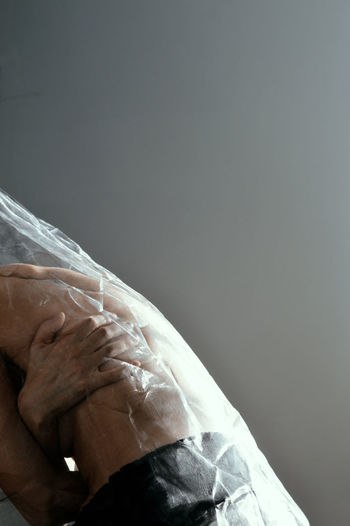 Midsection of shirtless woman wrapped in plastic against gray background