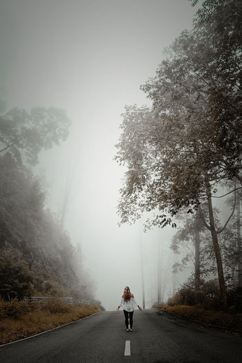 Rear view of woman standing on road during foggy weather against sky