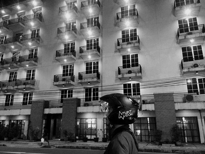 Rear view of man looking at illuminated building
