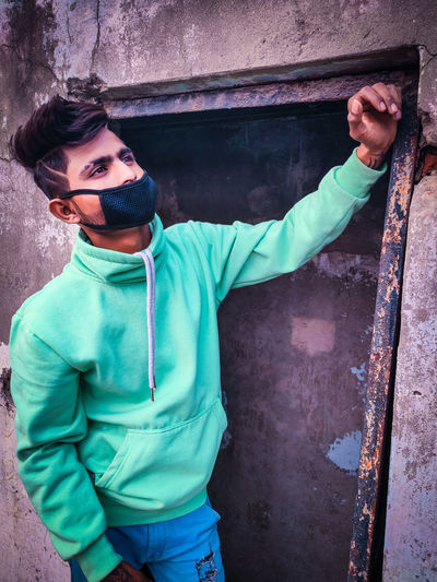 Young man wearing pollution mask while standing against wall