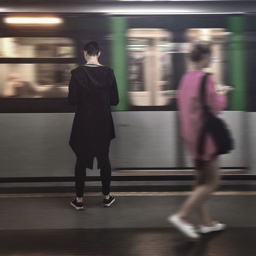 Rear view of woman standing nearby moving train