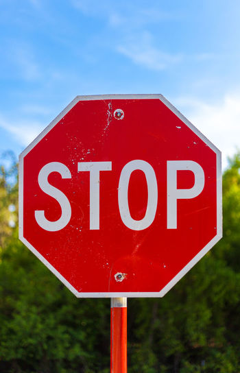 Stop sign against trees and blue sky Capital Letter Cloud - Sky Communication Day Geometric Shape Guidance Information Information Sign Interdiction Nature No People Outdoors Red Restriction Road Road Sign Sign Stop Sign Text Warning Warning Sign Western Script