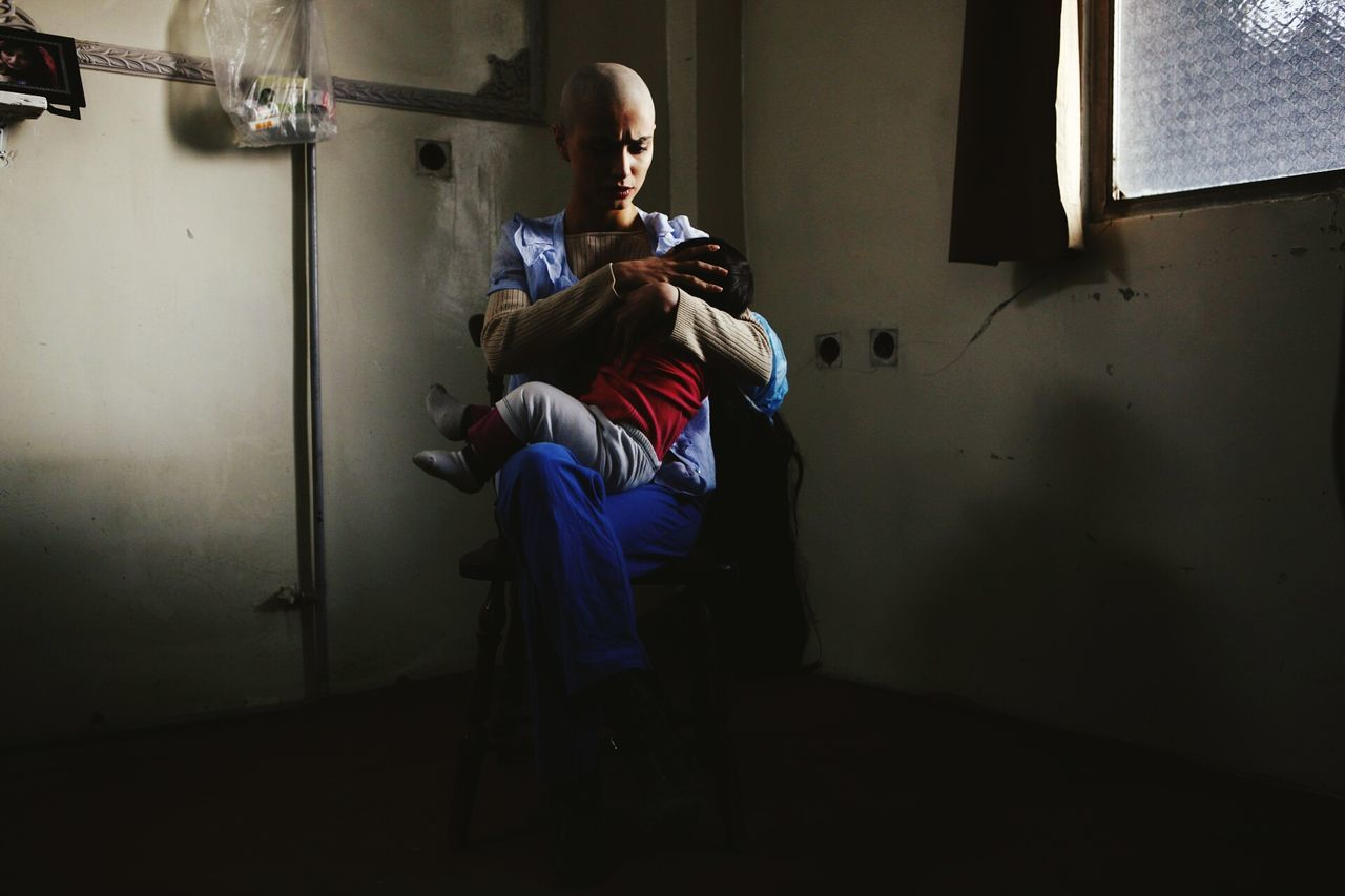 Woman with cancer holding child in dark room