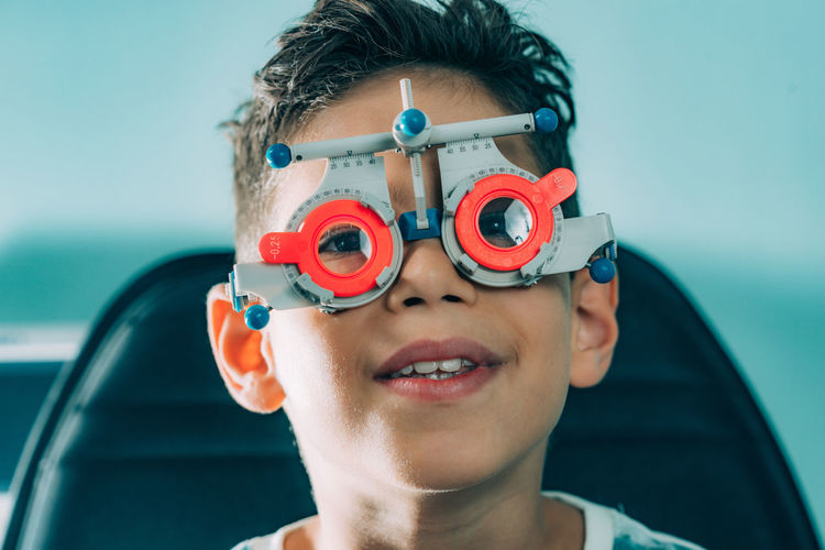 Close-up portrait of boy with eye test equipment