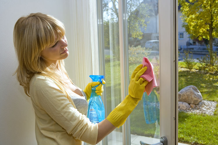 Side View Of Mid Adult Woman Cleaning Window At Home
