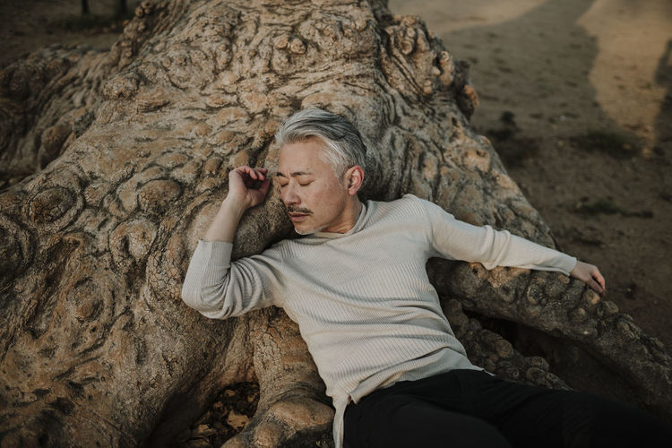 High angle portrait of man relaxing on rock