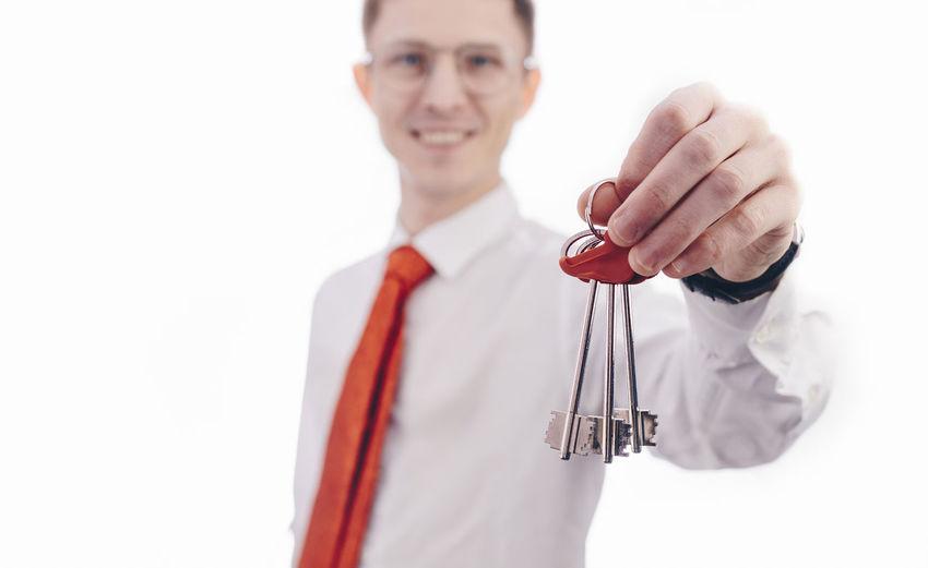 Portrait Of Smiling Real Estate Agent Holding House Keys Against White Background