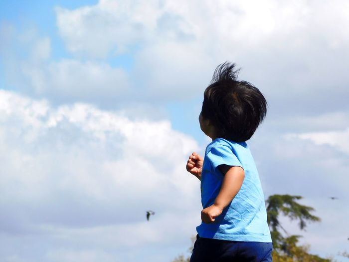 Rear view of boy running against cloudy sky