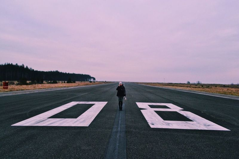 Man walking on airport runway against sky at sunset