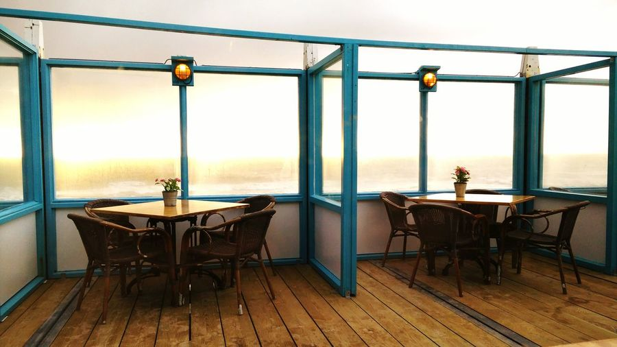 Empty Chairs And Tables Arranged At Cafe Against Sea During Sunset