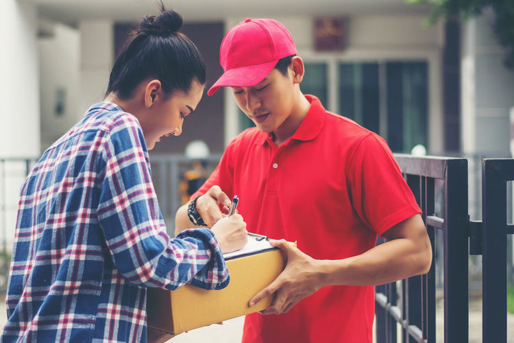 Female customer signing receipt while receiving package from delivery man at gate