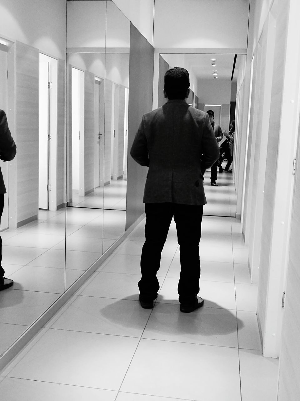 rear view, real people, full length, one person, indoors, men, tiled floor, standing, corridor, lifestyles, leisure activity, technology, day, one man only, architecture, people